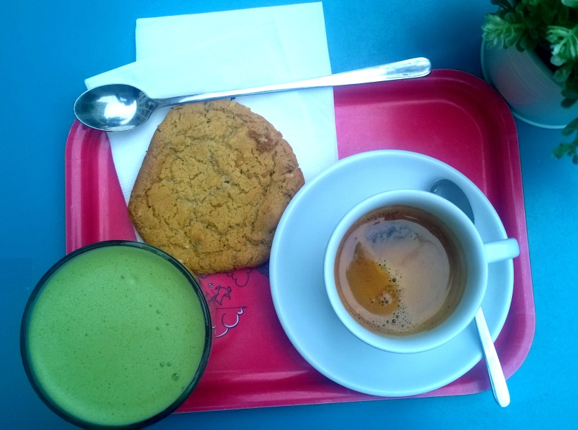 A photo of a matcha latte, espresso and a vegan cookie on a table, taken from above.