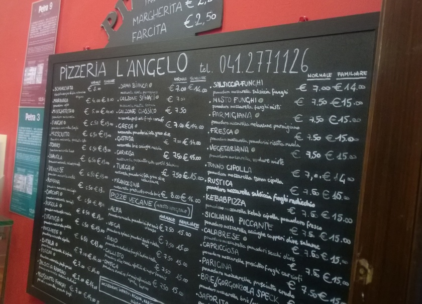 Menu board at pizzeria l'Angelo showing several vegan pizzas