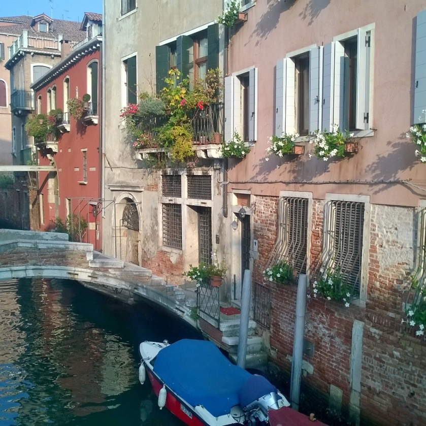 Boat, channel and houses in Venice